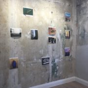 small photographic images on a rough painted wall by Marcos Chaves