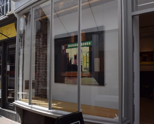 a painting called Budget Beers by Daniel Preece in the window of One Paved Court seen from the street