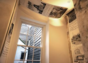 charcoal scroll drawing by Gabriela Shutz suspended from the gallery ceiling