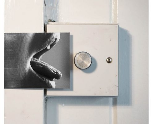 photograph of a mouth with tongue outstretched reaching towards a dimmer switch