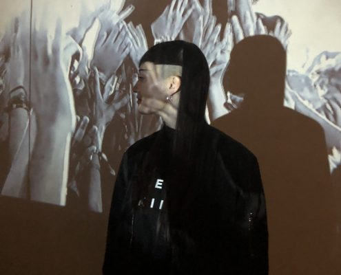 Hannah Marshall stands in front of a projection of a crowd at a concert. The projection covers her face.