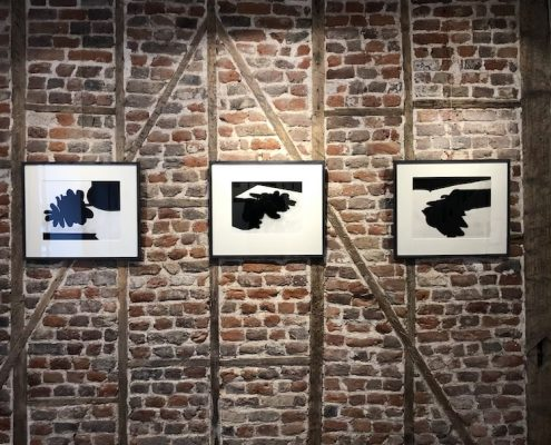 3 Peter Smith drawings on the exposed brick wall at One Paved Court