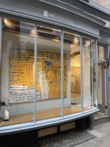 View of Oner Paved Court from the street showing large abstracrt yellow painting by Sandra Beccarelliin the window