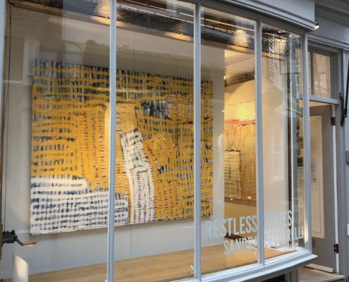 large abstract mainly yellow painting by Sandra Beccarelli, in the gallery window during her solo show, Restless States