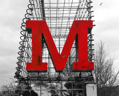 Large red M on gabion cage