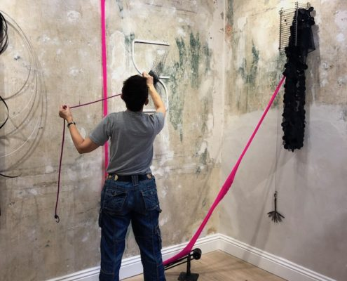 artist installing her work, photographed from behind.