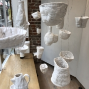installation in the windows of One Paved Court using stitched soft sculpture 'vessels' - bowls, cups, bottles, a jug and a teapot made from felted wool blankets covered with vintage linen and damask