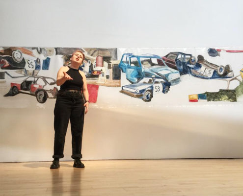 Amy Gillies, performance in front of drawings of cars