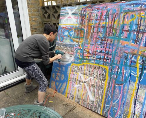 Artist Sandra Beccarelli creating artwork outside- drilling holes in a large colourful abstract canvas during lockdown
