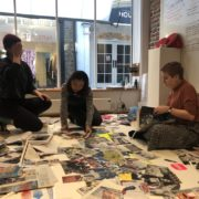 3 artists sitting on the floor during a collage Workshop at One Paved Court