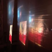 Projection in red and white across several layers of plastic sheeting