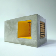 double concrete cube with glowing yellow interior and red ladder