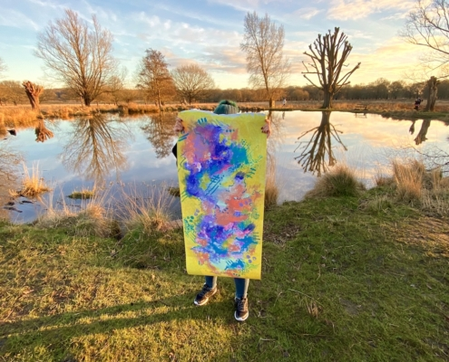 abstract painting being held up in front of a pond